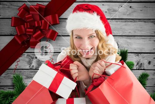 Excited woman in santa hat holding gifts during christmas time