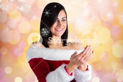 Woman in santa costume pretending to hold an imaginary snowflake