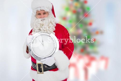 Santa claus holding wall clock showing few minutes to midnight