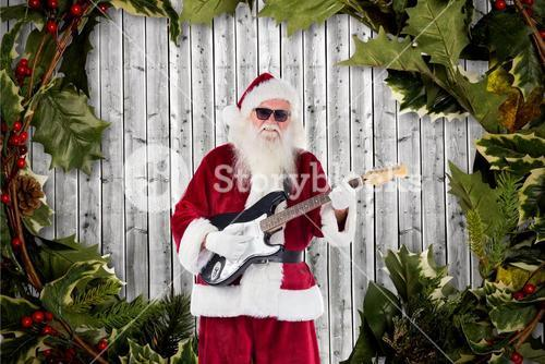 Santa claus playing guitar against digitally generated background