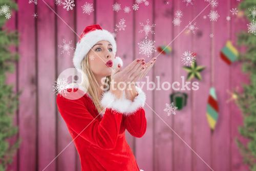 Woman in santa costume blowing imaginary snowflakes