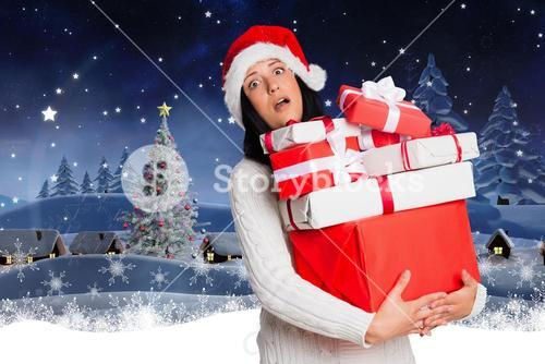 Confused woman in santa hat holding stack of christmas gifts