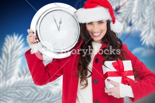 Woman in Santa hat holding gift and a wall clock showing few minutes to midnight