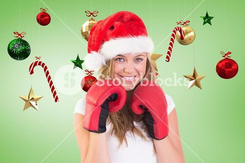 Woman in santa hat and boxing gloves against digitally generated background