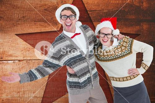 Happy couple in santa hat against digitally generated wooden background