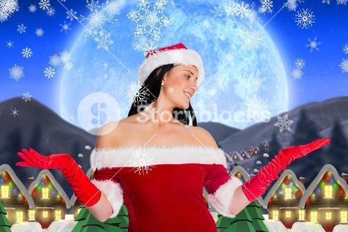 Smiling woman in santa costume pretending to catch imaginary snowflakes