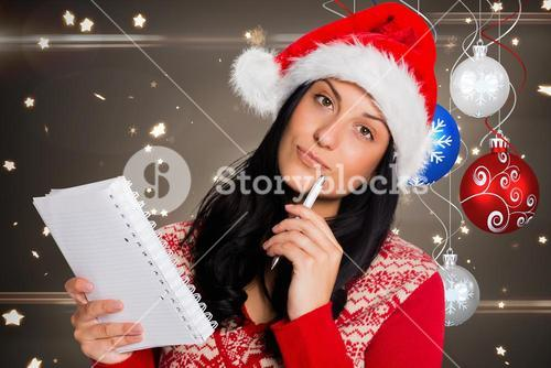 Thoughtful woman in santa hat holding pen and diary