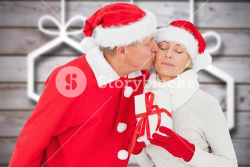 Man in santa hat kissing a woman holding gift