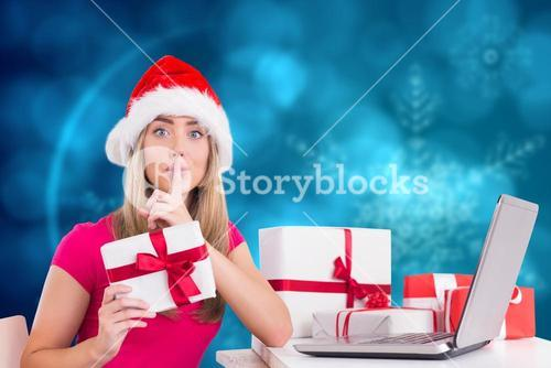 Woman with finger on lip holding christmas gift during christmas time