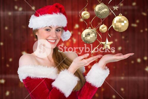 Beautiful woman in santa costume pretending to hold imaginary christmas decoration