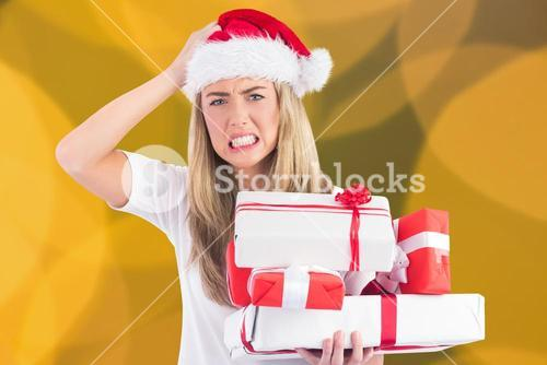 Frustrated woman in santa hat holding stack of gifts