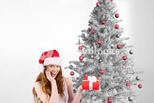 Happy woman in santa hat holding a gift against christmas background