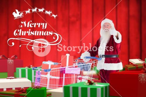 Santa claus showing thumbs up while holding shopping cart full of gifts
