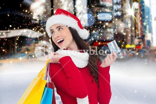 Cheerful woman in santa costume holding shopping bag and credit card