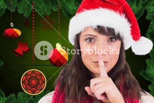Woman in santa hat with finger on lip against digitally generated christmas background