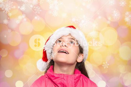 Cute girl in santa hat pretending to be amazed