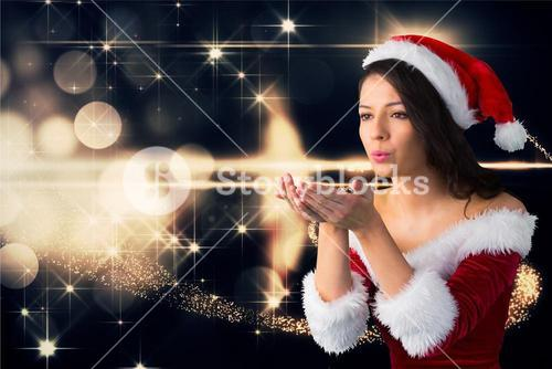 Beautiful woman wearing santa costume blowing a kiss against digitally generated christmas backgroun