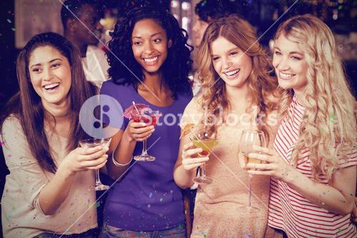 Composite image of friends drinking cocktails together while standing together