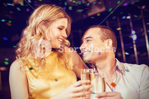 Composite image of couple toasting with champagne