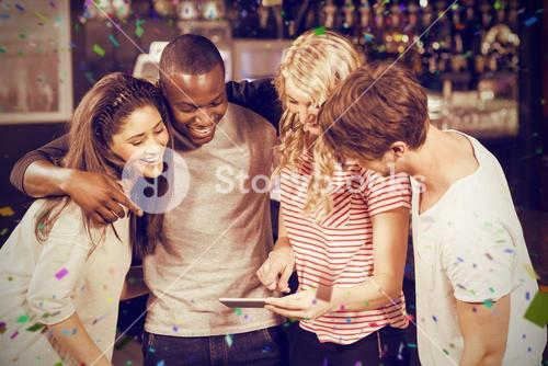 Composite image of happy friends looking at smartphone