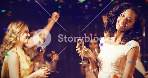 Composite image of happy friends holding champagne flute while dancing
