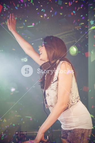 Composite image of side view of pretty female dj waving her hand while playing music