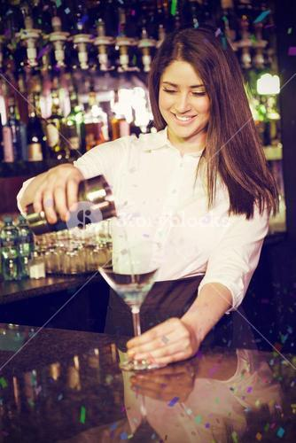 Composite image of pretty bartender pouring blue martini drink in glass