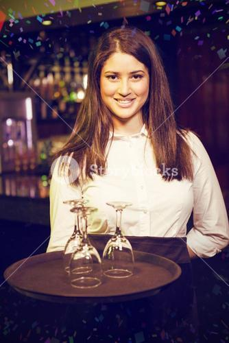 Composite image of portrait of waitress holding tray with wine glasses