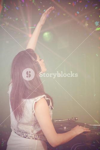 Composite image of pretty female dj waving her hand while playing music