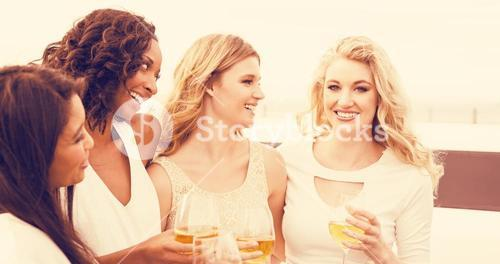 Women drinking wine next to limousine