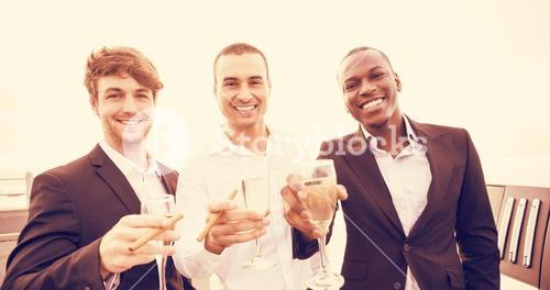 Portrait of well dressed men drinking champagne next to limousine