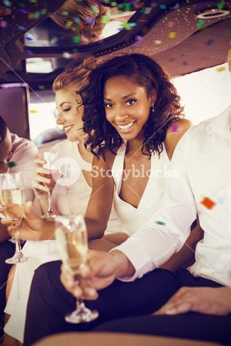 Composite image of well dressed woman drinking champagne in limousine