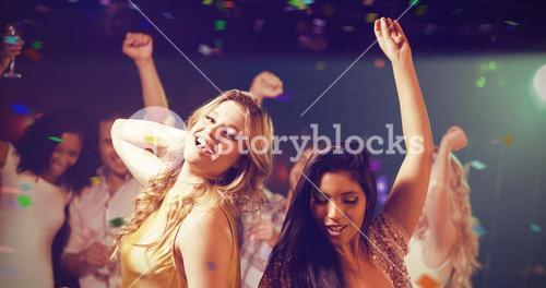 Composite image of friends holding champagne while dancing
