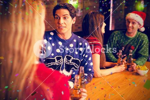 Composite image of friends having beers by table during christmas