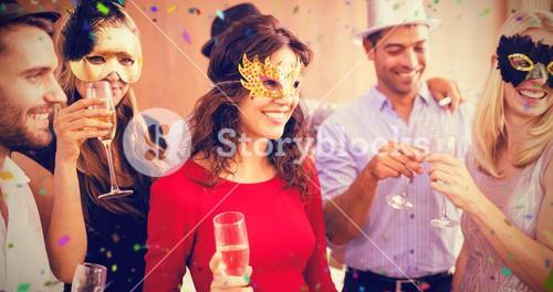 Composite image of friends with masks on holding champagne flute