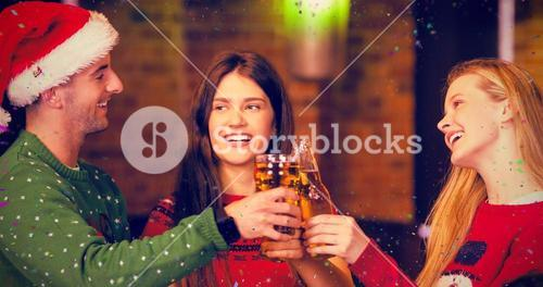 Composite image of cheerful friends having drinks during christmas