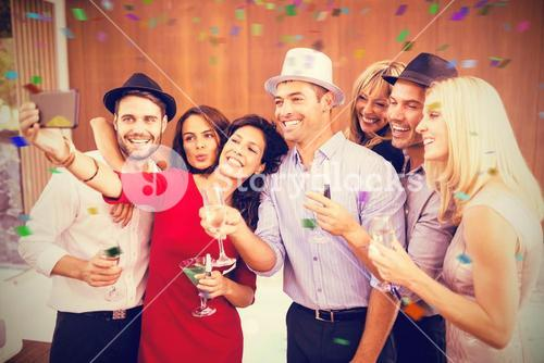 Composite image of cheerful woman taking selfie with friends