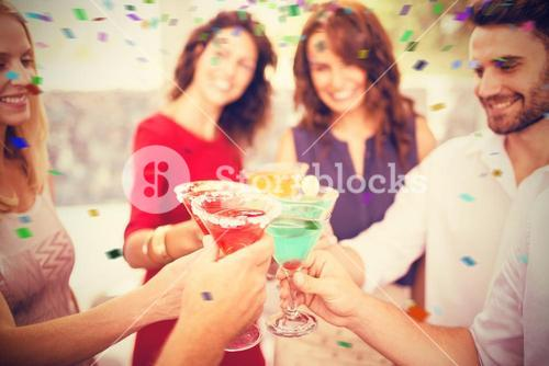 Composite image of cropped image of hand toasting cocktail