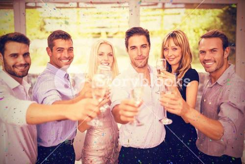 Composite image of portrait of friends holding champagne flute