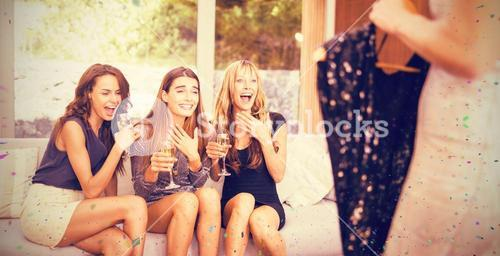 Composite image of happy women looking at their friends dress