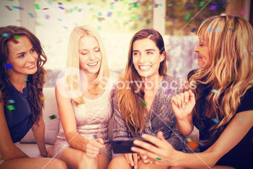 Composite image of beautiful women sitting together on sofa