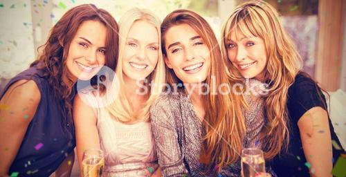 Composite image of portrait of beautiful women having drinks while sitting at sofa