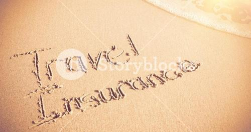 Travel Insurance written on sand