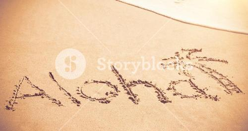 Aloha written text with palm tree on sand
