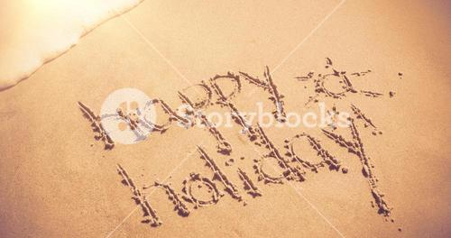 Happy holiday written on sand
