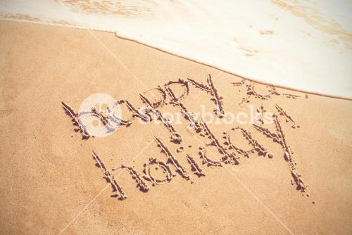 Happy holiday written text on sand