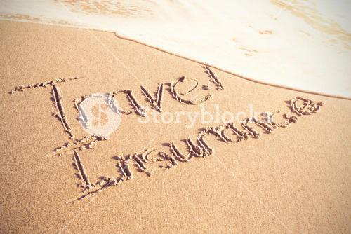 Travel Insurance text written on sand