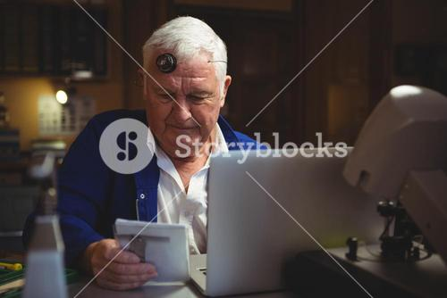 Horologist looking at notepad with laptop on table