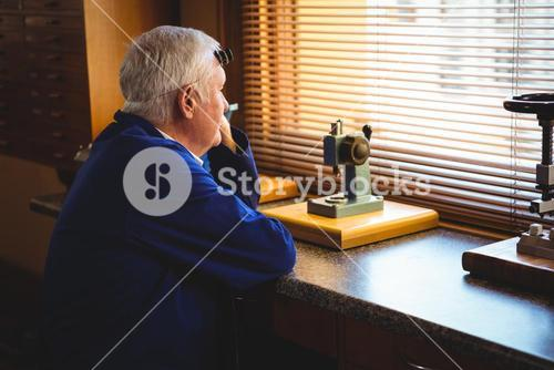 Thoughtful horologist looking through window