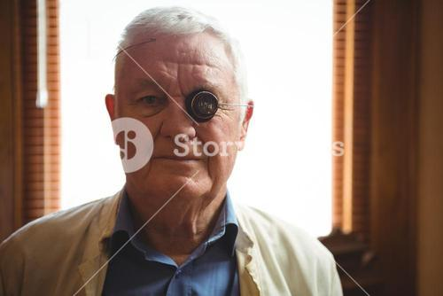 Portrait of horologist wearing magnifying glass